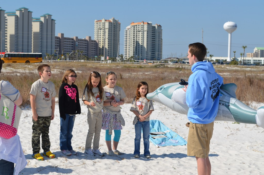 The next station the kids explored was all about dolphins. They learned about the parts of a dolphin, their habits, communication skills and some of the local efforts to help injured dolphins. The high school kid is using a giant inflatable dolphin to demonstrate its anatomy.