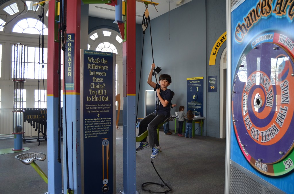 Jacob learns about the impacts of 2-, 3-, and 4-pulley systems. You sit in a seat and use the systems to hoist yourself up. The more pulleys in the system, the easier it is to do, but you lift yourself more slowly.